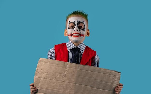 Ребенок держит пустой картон, изолированный на голубой стене. социальные проблемы и концепция людей. подготовка к хэллоуину.