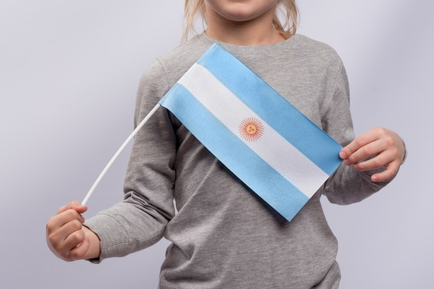 Child holds the flag of argentina in his hands. close up