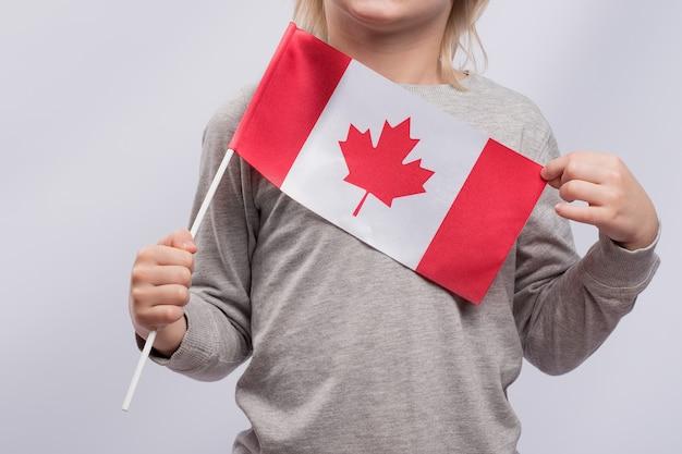 子供はカナダの旗を持っています。閉じる。カナダへの移民。子供のためのカナダでの教育。