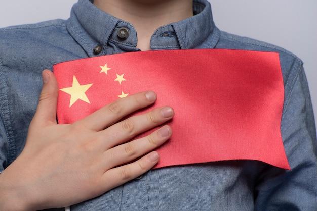 Ребенок держит флаг китая. закройте вверх. образование в китае. изучение китайского языка.