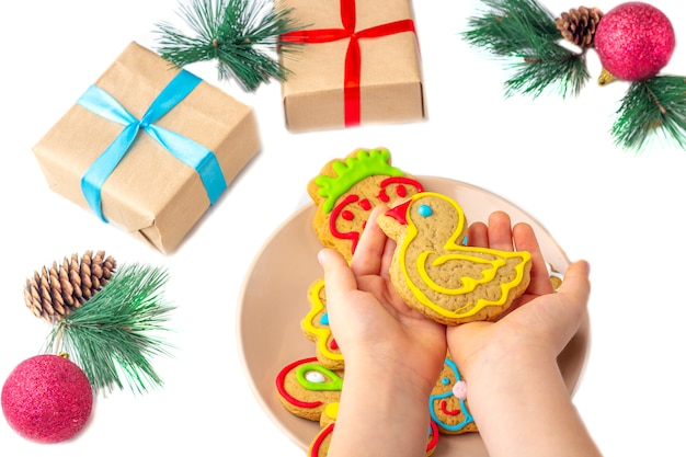 The child holds a gingerbread (cookie) on a white wooden background among fir branches and gifts. christmas and new year sweet gift concept. funny sweet food close-up.