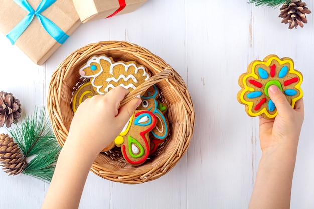 Child holds a homemade painted gingerbread (cookie) on white wooden background among fir branches and gifts. christmas and new year sweet gift concept. funny sweet food close-up.
