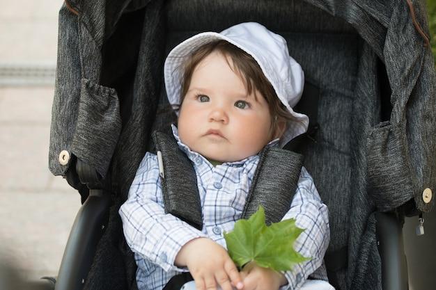 Ребенок держит кленовый лист. дитя и любовь к природе