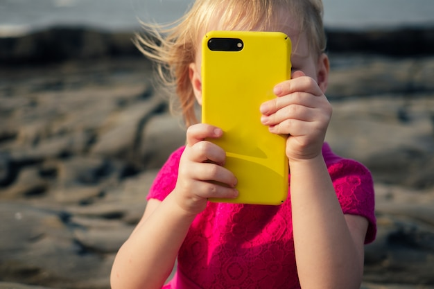 Child holds a phone in his hand