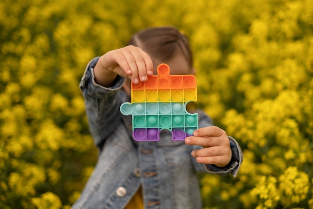 A child holds a popular toy popit in the form of a rapeseed field puzzle