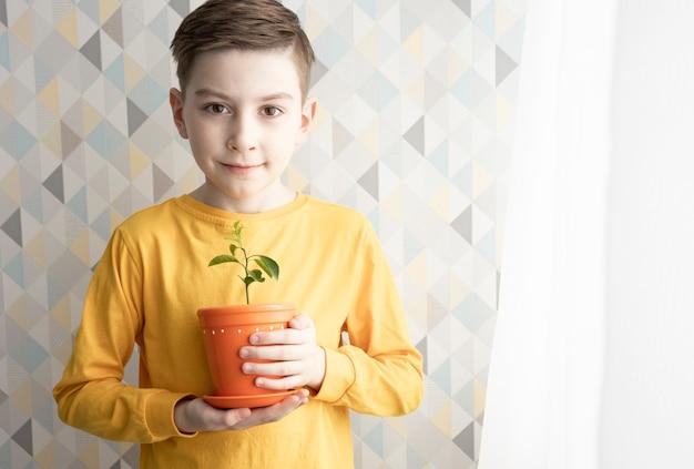 子供は手に顕花植物とポットを持っています。家の背景