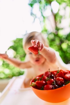Child holds strawberry in hand while sitting in front of a bowl of fruits