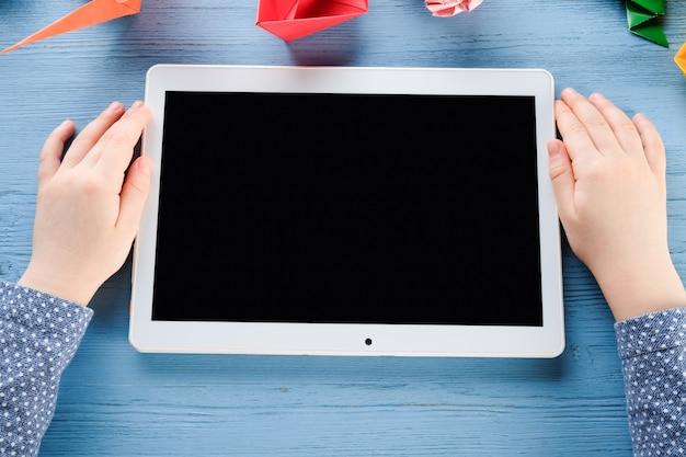 The child holds a tablet in his hands. hands of a child with a tablet.