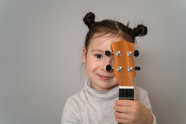 A child holds a ukulele in his hands. small creative children. girl learns to play an instrument online. creative child holding a guitar near his face