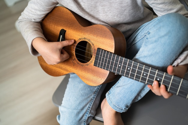 A child holds a ukulele in his hands. small creative children. girl learns to play an instrument online.