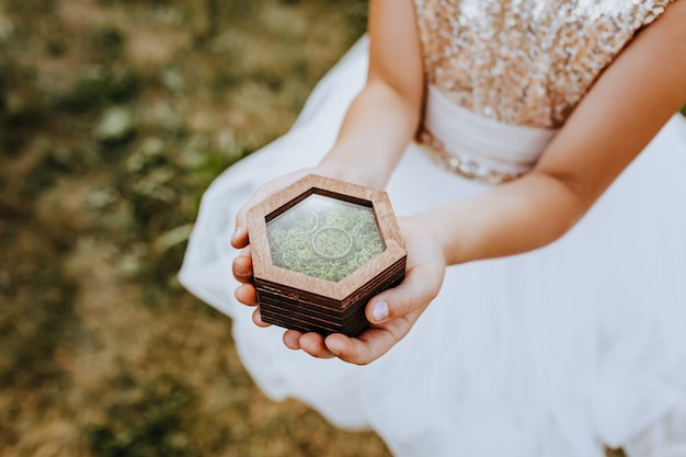 A child holds with his hands two wedding rings in a wooden box with a plant moss