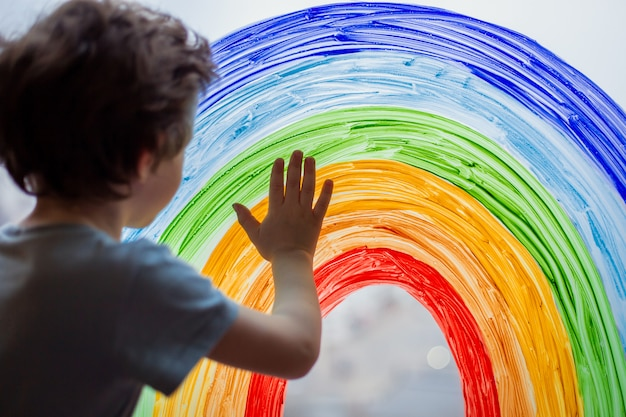 Child at home draws a rainbow on the window.