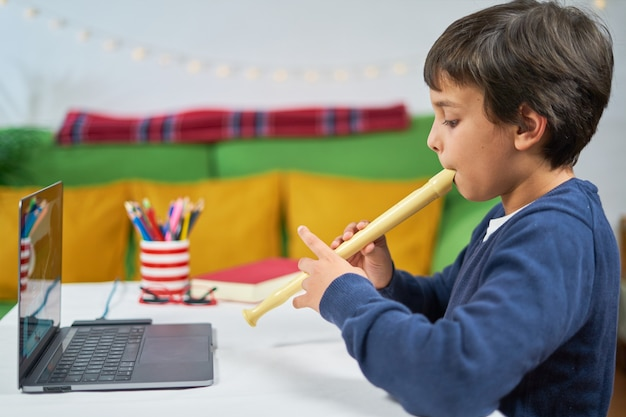 Child at home learning to play the flute with an online teacher connected with the laptop