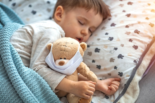 Child in home quarantine at the bed, sleeping, with medical mask on his sick teddy bear, for protection against viruses during coronavirus covid-19 and flu outbreak