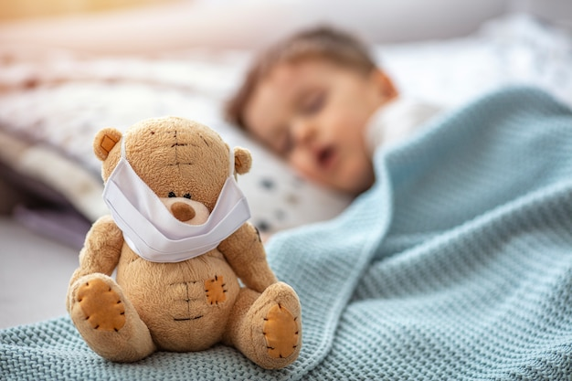 Child in home quarantine at the bed, sleeping, with medical mask on his sick teddy bear, for protection against viruses during coronavirus