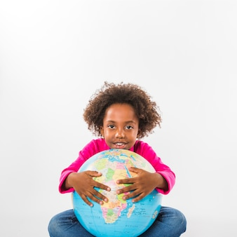 Child hugging globe in studio