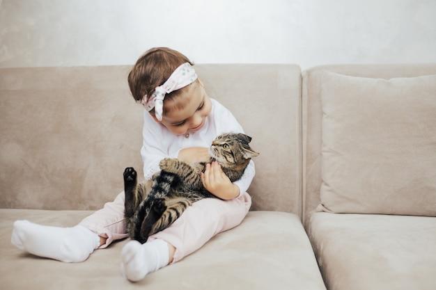 Ребенок обнимает своего кота на диване у белой стены