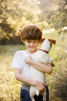 Child hugging her friend a puppy in outdoors.