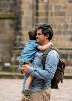 旧市街の通りを歩いている間、子供は父親を抱擁します。
