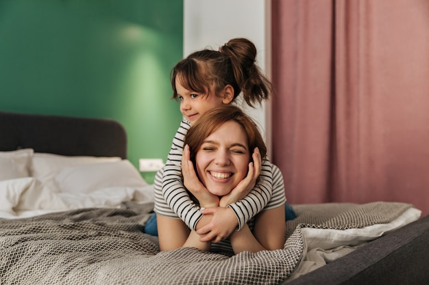 Child hugs mom. woman and her daughter lie on bed.
