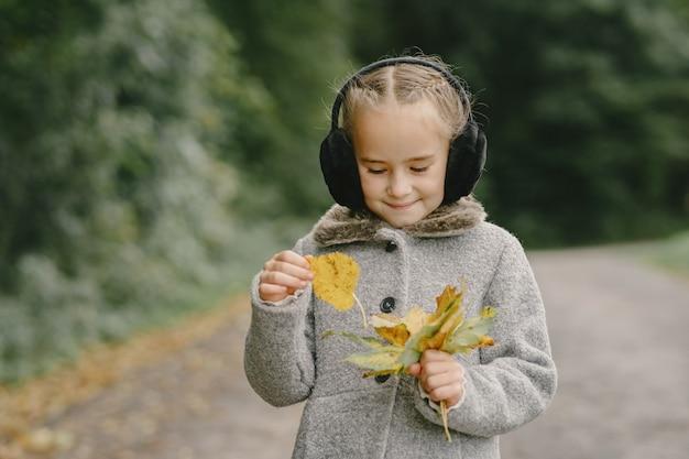 秋の公園の子供。灰色のコートを着た子供。