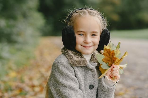 Ребенок в осеннем парке. малыш в сером пальто.