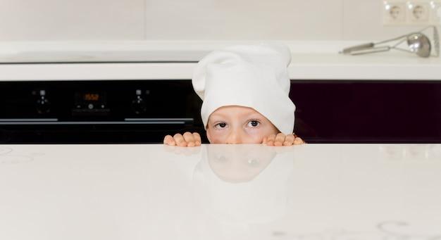 카운터 뒤에 숨어 요리사 모자에 아이
