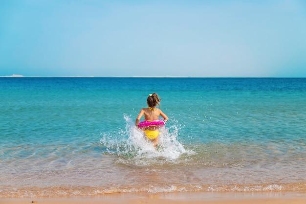 Ребенок в кругу плавает в море.