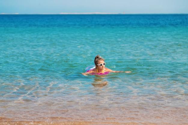 輪になっている子供は海で泳ぎます。