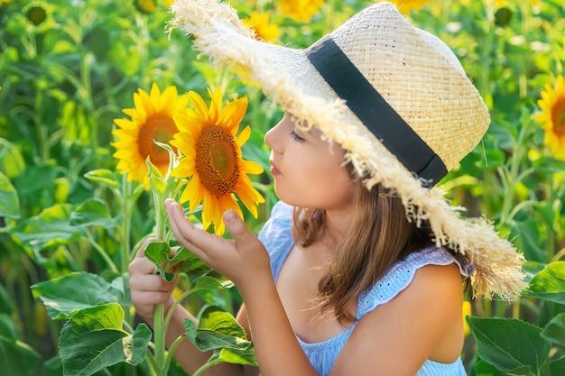 Ребенок в поле цветущих подсолнухов