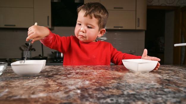 Ребенок в шляпе санты готовит новогодний ужин