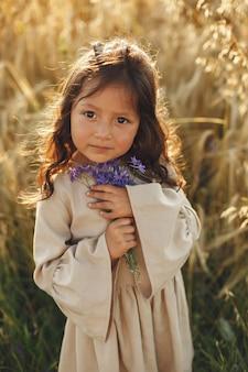 Ребенок в летнем поле. маленькая девочка в милом коричневом платье.