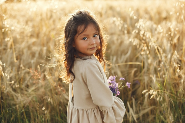 여름 필드에서 아이입니다. 귀여운 갈색 드레스에 어린 소녀입니다.