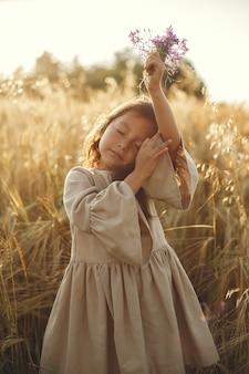 夏の畑の子。かわいい茶色のドレスの少女。