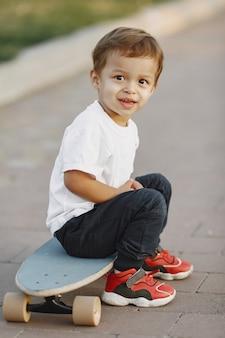 Ребенок в летнем парке. мальчик в белой футболке. малыш с коньком.