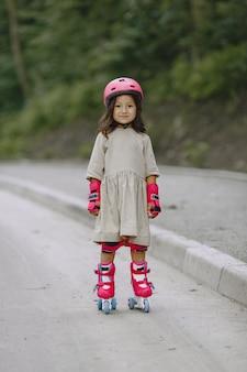 夏の公園の子。ピンクのヘルメットをかぶった子供。ローラーを持つ少女。
