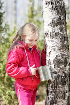 Ребенок на дереве, собирающий березовый сок