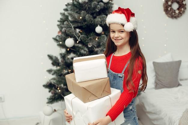 Ребенок в белом свитере. дочь сидит возле елки.