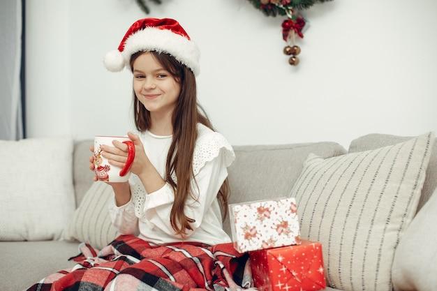 白いセーターを着た子供。クリスマスツリーの近くに座っている娘。