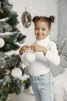 Ребенок в белом свитере. дочь стоит возле елки.