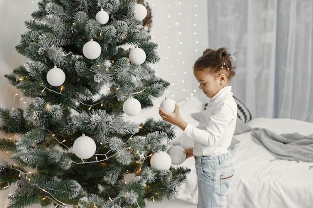 白いセーターを着た子供。クリスマスツリーの近くに立っている娘。