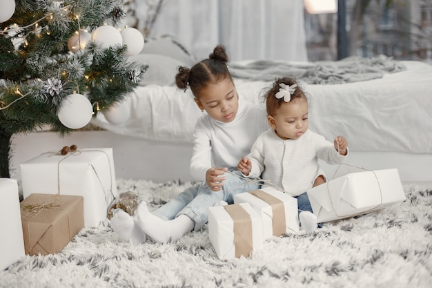 白いセーターを着た子供。クリスマスツリーの近くに座っている娘。家に2人の姉妹。
