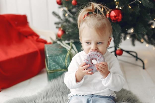 白いセーターを着た子供が遊んでいます。娘がクリスマスツリーの近くに立っています。