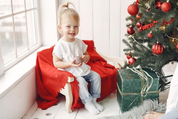 白いtシャツを着た子供が遊んでいます。クリスマスツリーの近くに座っている娘。