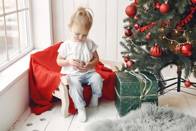 Играет ребенок в белой футболке. дочь сидит возле елки.