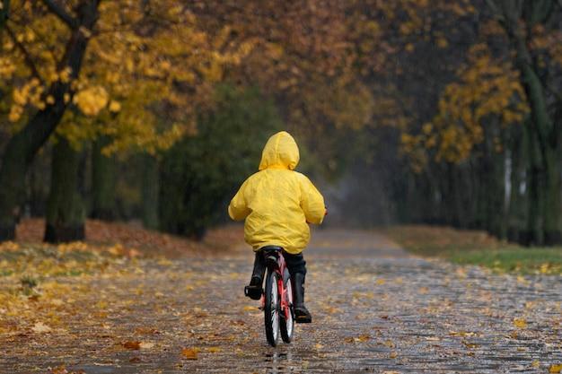Ребенок в желтом плаще катается на велосипеде в безлюдном парке. дождливый город. вид сзади.