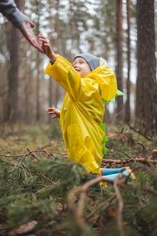 雨上がりの森の中を歩く黄色いレインコートを着た子供が松の枝で地面に座り、お母さんが手を伸ばして起き上がるのを手伝う