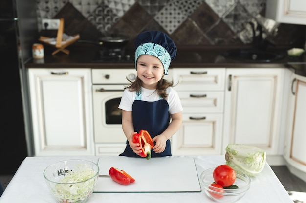 Ребенок в фартуке и поварской шляпе на кухне готовит салат