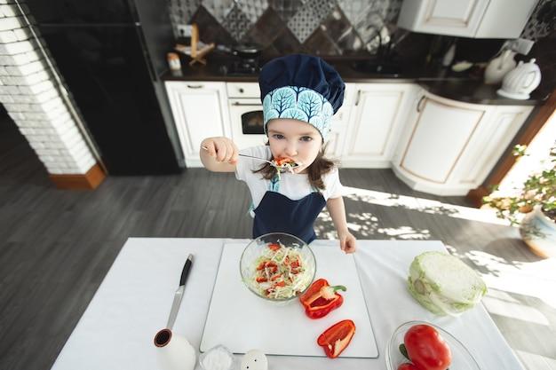 Ребенок в фартуке и шляпе шеф-повара ест овощной салат на кухне
