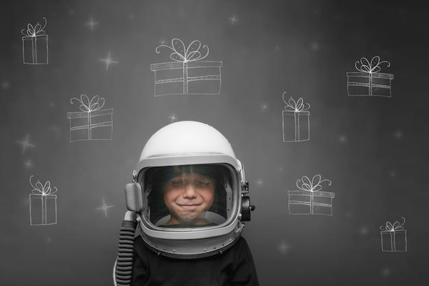 Ребенок в шлеме космонавта мечтает о рождестве и подарках